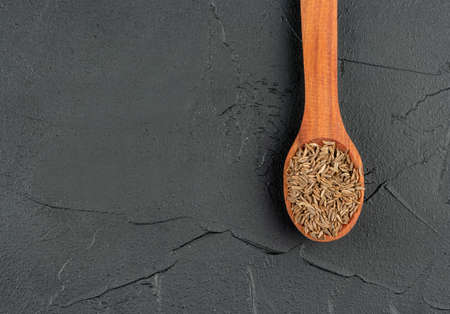 Spice dry cumin in wooden spoon on empty dark background closeup