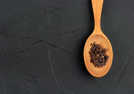 Large wooden spoon with dry cloves on dark background, top view