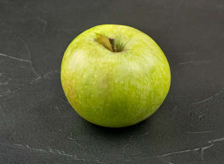Ripe green apple fruit on a dark background