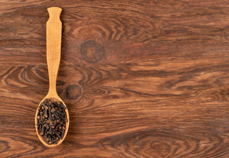 Spoon with dry cloves on wooden background, top view Фото со стока - 128717256