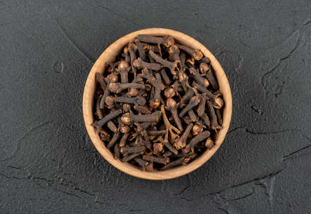 Wooden bowl of dry cloves on a dark background, top view Фото со стока - 128717255