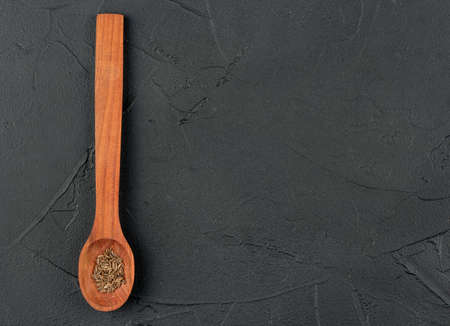 Spice dry cumin in wooden spoon on empty dark background