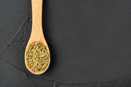Small wooden spoon with dry rosemary close-up on dark background