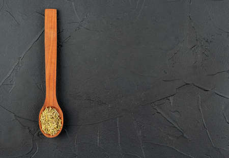 Small spoon with the dry rosemary on the empty concrete background