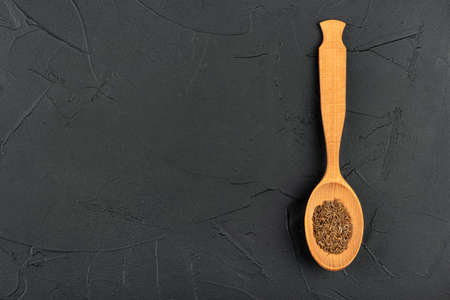 Large spoon with dry cumin on an empty dark concrete background Фото со стока