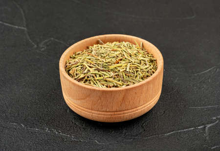 Wooden bowl with dry rosemary on dark background
