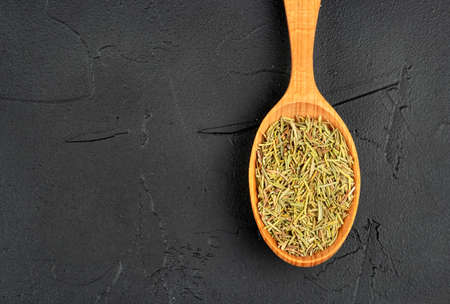 Dry rosemary in a wooden spoon close-up on a dark background Stockfoto