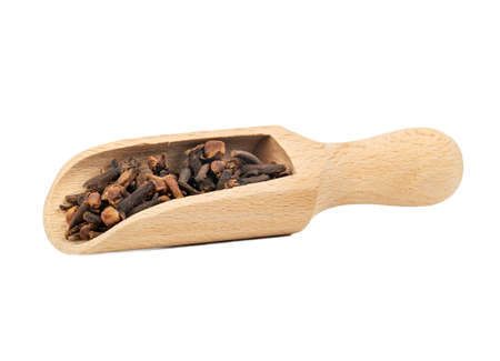 Dry cloves in a wooden scoop on a white background