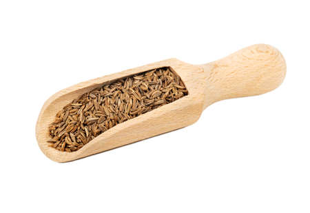 Seasoning caraway seeds in a wooden scoop on white background Фото со стока