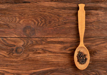 Seasoning dry cloves in a spoon on an empty wooden background, top view Фото со стока - 129712213