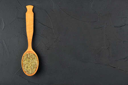 Dry rosemary in a wooden spoon on an empty concrete background