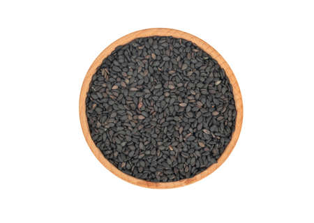 Wooden bowl with black sesame seeds isolated on white background, top view Фото со стока