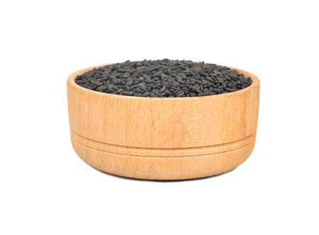Wooden bowl with black sesame seeds isolated on white background