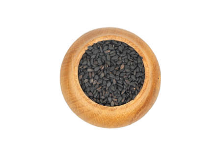 Black sesame in wooden container isolated on white background, top view