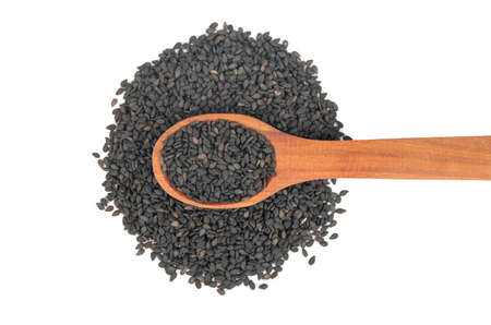 Wooden spoon on a pile of black sesame seeds on a white background