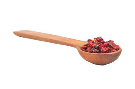 Dry red barberry in wooden spoon isolated on white background