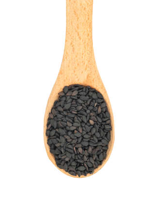Small spoon with black sesame close up on white background, top view