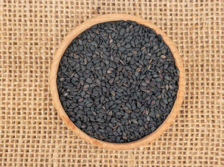 Black sesame seeds in a bowl on a burlap, top view