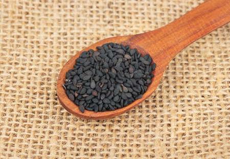 Spoon with black sesame seeds on burlap closeup