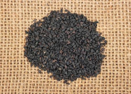 Pile of black sesame seeds closeup on burlap, top view
