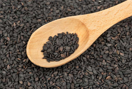 Pile of scattered black sesame seeds with a wooden spoon close up Stockfoto