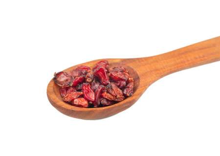 Wooden spoon with dry red barberry on white background close up
