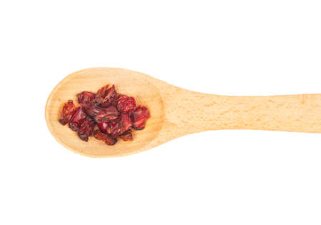Dry barberry in a small wooden spoon isolated on white background closeup, top view