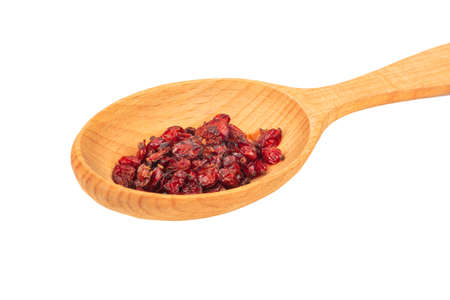 Dry barberry berries in wooden spoon close up on white background