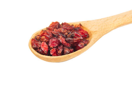 Dry barberry in a small wooden spoon isolated on white background closeup
