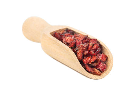 Wooden scoop with dry barberry on white background Фото со стока