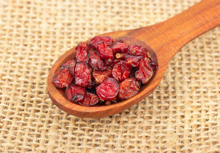 Spoon with dry barberry on burlap close-up
