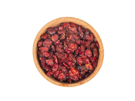 Dry barberry in wooden bowl on white background, top view