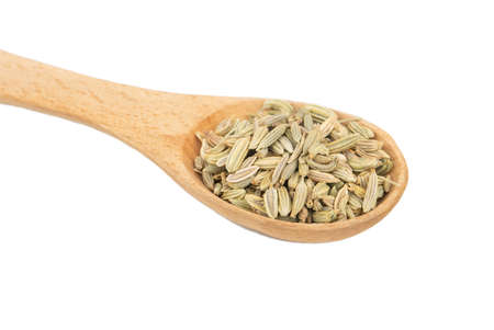 Dry fennel grains in wooden spoon closeup on white background