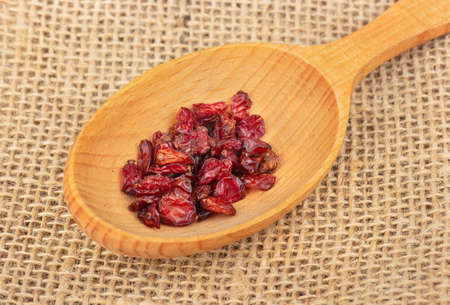 Wooden spoon with dry barberry on burlap