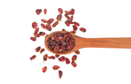 Scattered dry barberry berries in a spoon on a white background