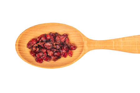 Dry barberry berries in wooden spoon close up on white background, top view