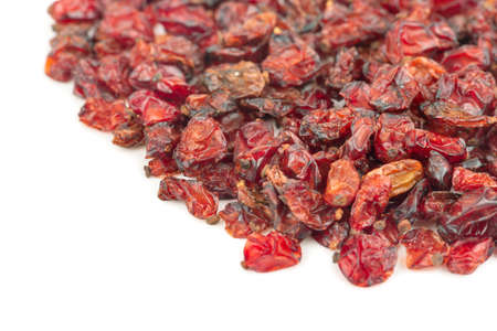 Scattered red berries of dry barberry on a white background Фото со стока