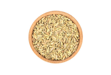 Wooden bowl with dry fennel isolated on white background, top view Фото со стока