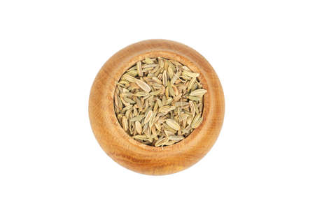 Spice dry fennel in wooden container isolated on white background, top view