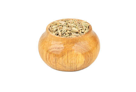 Spice dry fennel in wooden container isolated on white background Фото со стока