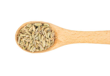 Dry fennel grains in wooden spoon on white background, top view Фото со стока