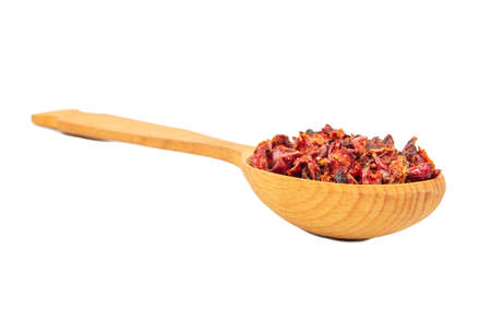 Pieces of dry red pepper in a large spoon isolated on white background Фото со стока