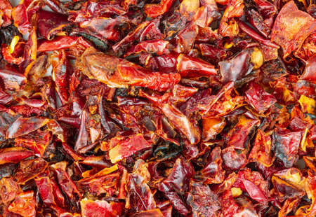 Background of pieces of dry red pepper closeup Фото со стока