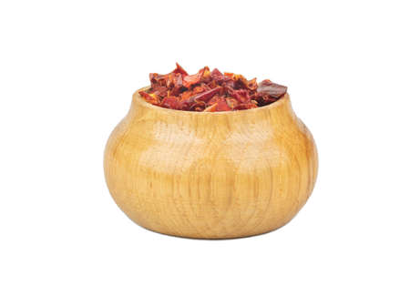 Pieces of dry red pepper in a wooden container on a white background