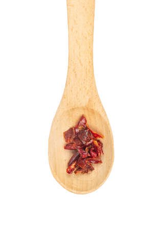 Pieces of dry red pepper in a small spoon on a white background, top view