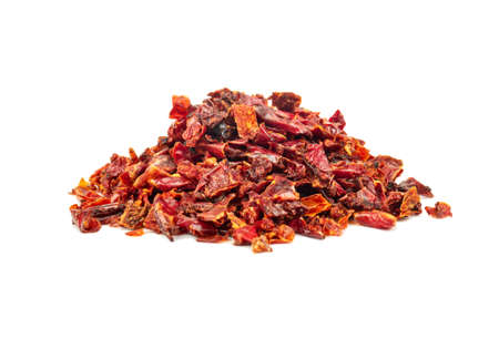 Pile of pieces of dry red pepper on a white background