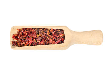 Wooden scoop with pieces of dry red pepper on white background, top view Фото со стока