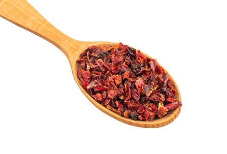 Large wooden spoon with pieces of dry red pepper on a white background, top view