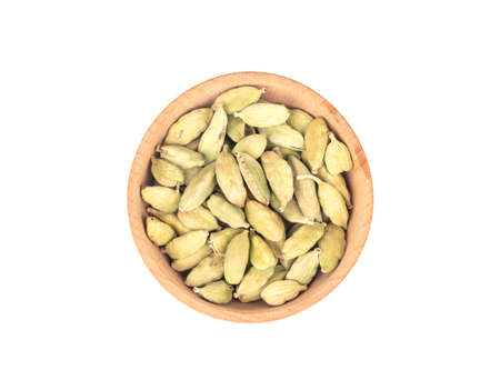 Dry cardamom in wooden bowl isolated on white background, top view