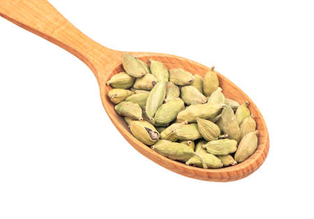 Large wooden spoon with dry cardamom isolated on white background closeup Zdjęcie Seryjne